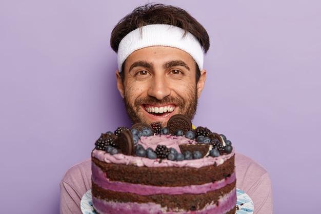 Zdjęcie w głowę przystojnego, nieogolonego mężczyzny, który jest zadowolony z otrzymania dużego pysznego ciasta owocowego