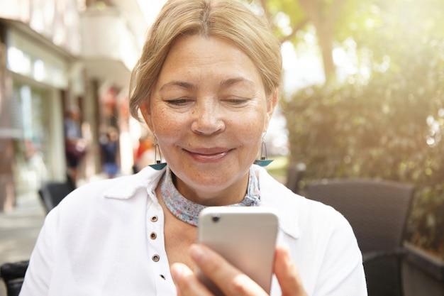 Zdjęcie w głowę szczęśliwej blond kobiety w wieku o jasnych włosach i pięknym uśmiechu, patrzącej na ekran swojego elektronicznego gadżetu, komunikującej się z dziećmi w internecie za pomocą smartfona, siedzącej w kawiarni na świeżym powietrzu