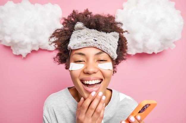 Zdjęcie w głowę wesołej kobiety z kręconymi włosami uśmiecha się szeroko, śmiejąc się z czegoś ubranego w ubrania domowe, używa nowoczesnego telefonu komórkowego do surfowania w sieci społecznościowej
