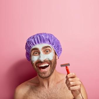 Zdjęcie w głowę zadowolonego młodego mężczyzny trzymającego brzytwę do golenia, nakładającego glinkową maseczkę na twarz, nosi czepek kąpielowy, wykonuje zabiegi higieniczne i pielęgnacyjne, dba o siebie, stoi nago samotnie, pokazuje białe równe zęby