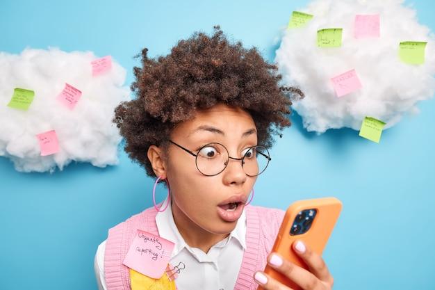 Zdjęcie w głowę zszokowanej kobiety z kręconymi włosami wpatrującej się w ekran smartfona dowiaduje się, że nie zdała egzaminu ma dużo pracy, przypomina notatki na naklejkach, przygotowuje raport pilnie izoluje na niebieskiej ścianie