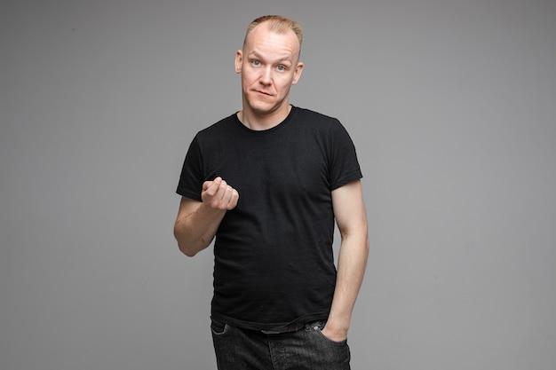 Zdjęcie w pasie dorosłego mężczyzny w czarnej koszuli, wykonując ręką gest ostrzegawczy