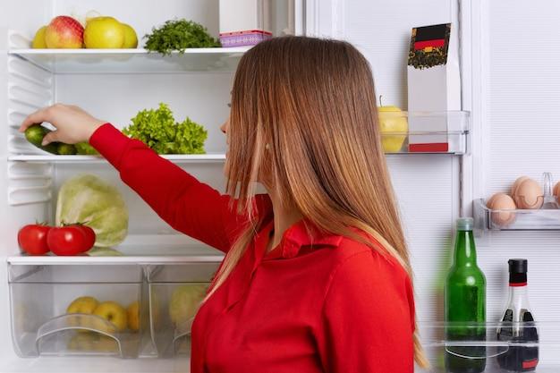 Zdjęcie w pomieszczeniu młodej kobiety o długich prostych ciemnych włosach, stawia warzywa na półce lodówki, je tylko zdrowe jedzenie. kobieta w kuchni gospodyni zamierza zrobić sałatkę z warzyw.