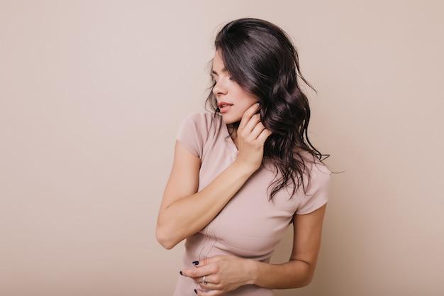 Zdjęcie w pomieszczeniu opalonej kobiety z niebieskim manicure. dziewczyna z falistymi lśniącymi włosami pozowanie w profilu.