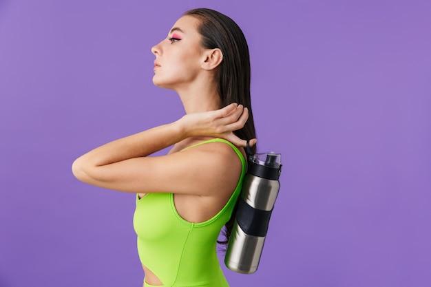 Zdjęcie w profilu ładnej pięknej kobiety z jasnym makijażem trzymającej butelkę wody