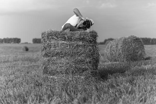 Zdjęcie w terenie letnia sesja zdjęciowa w terenie fotograf w kapeluszu siedzi