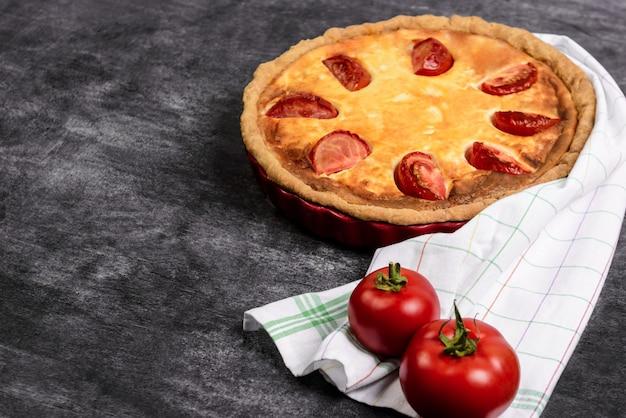 Zdjęcie warzywne ciasto z pomidorami na bok na szarej powierzchni