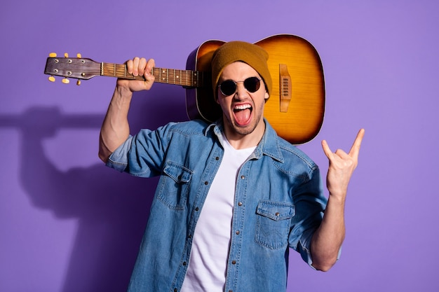 Zdjęcie wesołego atrakcyjnego rockera krzyczącego modnie pokazującego ci rockowe palce z rogami trzymającego gitarę akustyczną w ramieniu w dżinsowych okularach na białym tle fioletowy żywy kolor tła