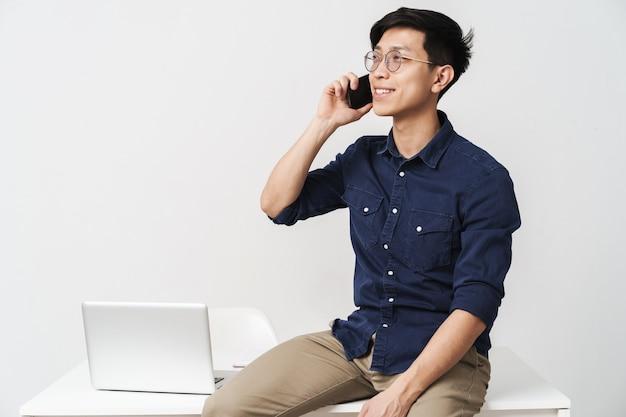 Zdjęcie wesołego azjatyckiego biznesmena w okularach, siedzącego przy stole i rozmawiającego na smartfonie podczas pracy z laptopem w biurze na białym tle nad białą ścianą