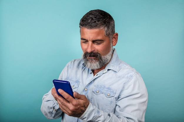 Zdjęcie wesołego brodatego mężczyzny używającego smartfona na niebieskim tle