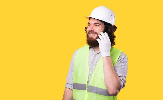 Zdjęcie wesołego młodego architekta rozmawiającego przez telefon odwraca wzrok w pobliżu żółtej ściany