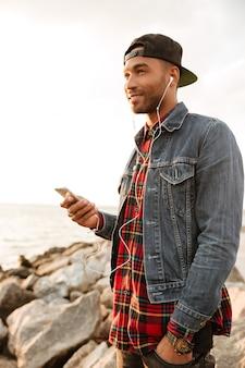 Zdjęcie wesołego młodego mężczyzny w czapce spacerującego po plaży i rozmawiającego przez telefon podczas słuchania muzyki
