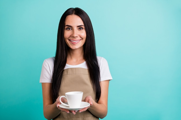 Zdjęcie wesołego pozytywnego, ładnego, całkiem miłego baristy, który daje zamówioną filiżankę herbaty w pobliżu pustej przestrzeni na białym tle w żywych kolorach