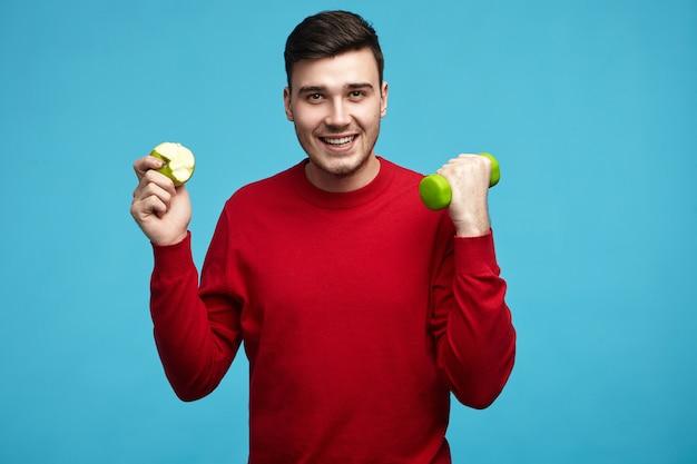 Zdjęcie wesołego, uroczego faceta po dwudziestce, próbującego schudnąć