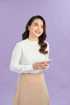 Zdjęcie wesołej bizneswoman uśmiechniętej i używającej telefonu komórkowego odizolowanego na fioletowym tle