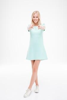 Zdjęcie wesołej damy ubranej w niebieską sukienkę i wskazującej na przód na białym tle nad białą ścianą