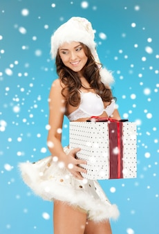 Zdjęcie wesołej dziewczyny pomocnika świętego mikołaja w bieliźnie z pudełkiem prezentowym