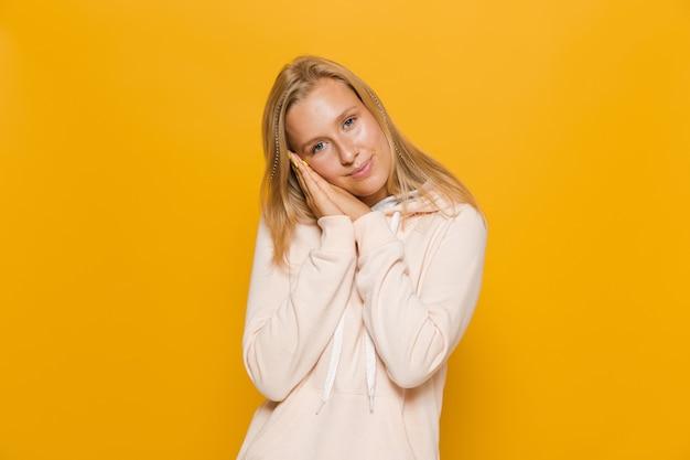 Zdjęcie wesołej dziewczyny w wieku 16-18 lat z aparatem ortodontycznym uśmiecha się do kamery, odizolowane na żółtym tle