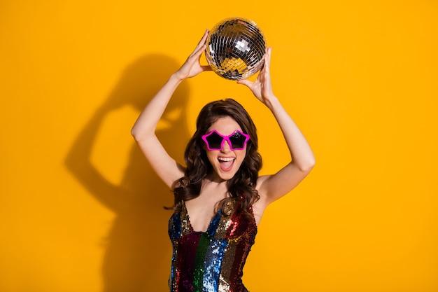 Zdjęcie wesołej energicznej dziewczyny imprezowej trzymać brokat świecące kula dyskotekowa cieszyć się radować taniec klub nocny nosić błyszczącą spódnicę okulary w kształcie gwiazdy na białym tle nad żywym kolorem tła