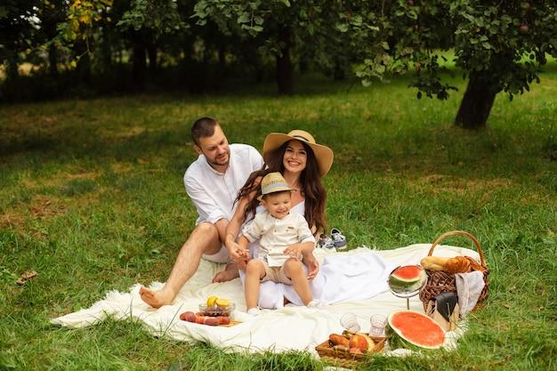 Zdjęcie wesołej kaukaskiej mamy, taty i ich dziecka wspólnie się bawią i uśmiechają w ogrodzie