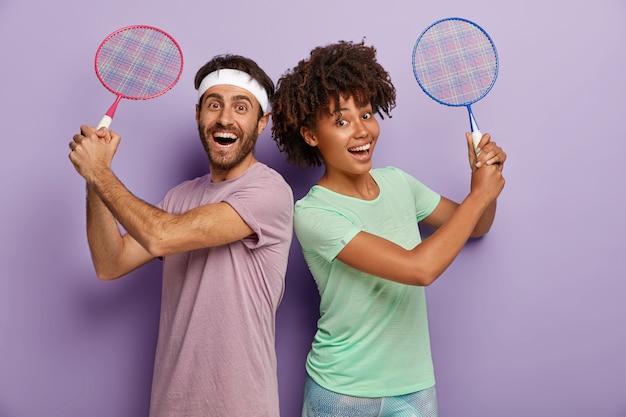 Zdjęcie wesołej kobiety i mężczyzny rasy mieszanej stoją do siebie plecami, trzymają rakietę tenisową, bawią się, śmieją się pozytywnie, ubrani w koszulki, są aktywni i zadowoleni