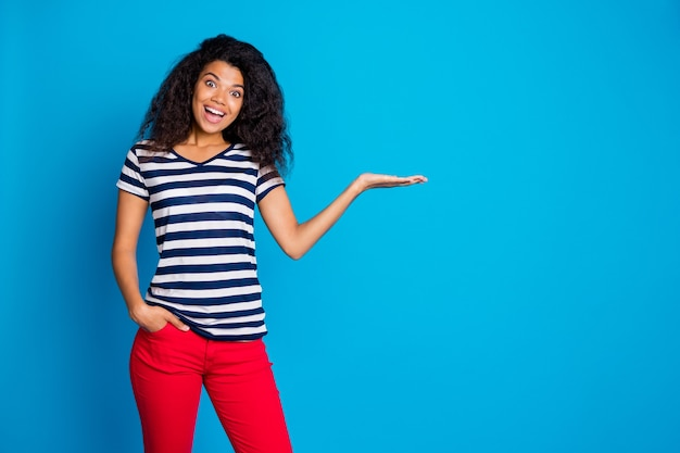 Zdjęcie wesołej kobiety ręka w kieszeni trzyma coś, prezentacja produktu, miejsce na niebieską ścianę