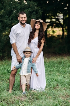 Zdjęcie wesołej mamy rasy kaukaskiej, taty i ich dziecko razem bawią się i uśmiechają w ogrodzie