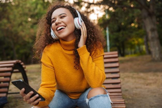 Zdjęcie wesołej optymistycznej pięknej młodej kobiety kręcone siedzieć na ławce w parku na zewnątrz słuchania muzyki w słuchawkach przy użyciu telefonu komórkowego.