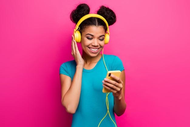 Zdjęcie wesołej pani trzymającej telefon za pomocą nowoczesnych słuchawek