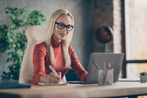 Zdjęcie wesołej, pozytywnej, inteligentnej, mądrej kobiety, uśmiechającej się ząbkiem, zaglądającej w zamyśleniu w laptopie analizującej informacje i notującej najważniejsze szczegóły