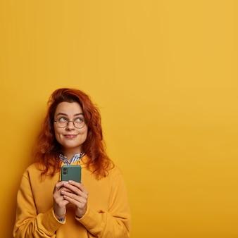 Zdjęcie wesołej, radosnej tysiącletniej dziewczyny o rudych włosach używa telefonu komórkowego do wysyłania smsów, myśli o treści wiadomości dla kochanka