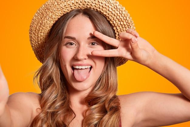 Zdjęcie wesołej rasy białej z zabawną miną, czyni znak pokoju, pokazuje język, robi selfie, nosi elegancki słomkowy kapelusz, pozuje na pomarańczowej ścianie. koncepcja ludzi i rekreacji