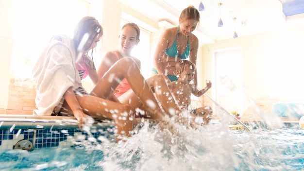 Zdjęcie wesołej roześmianej rodziny z dziećmi rozpryskiwania wody z nogami na krytym basenie. rodzinne zabawy i zabawy na basenie