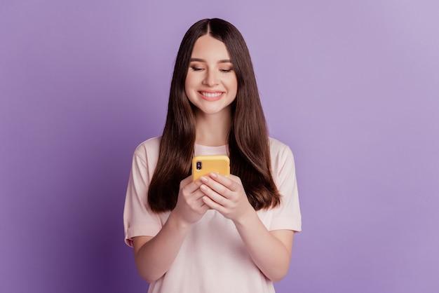 Zdjęcie wesołej słodkiej młodej kobiety trzymaj telefon komórkowy na czacie sms wygląd ekranu
