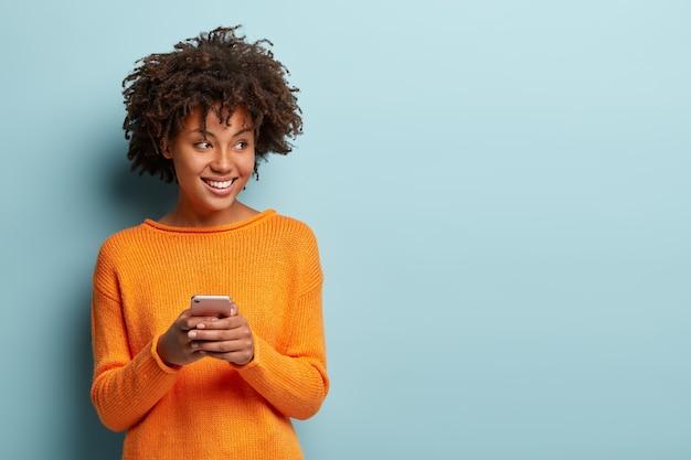 Zdjęcie wesołej, zachwyconej afroamerykanki pisze sms na nowoczesnym urządzeniu telefonii komórkowej, cieszy się dobrym połączeniem internetowym