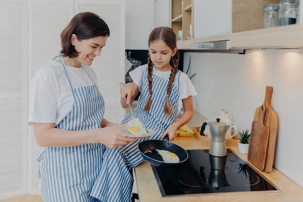 Zdjęcie wesołej zajętej mamy i jej córki pozujących w pobliżu pieca, serwujących śniadanie dla rodziny, smażenia jajek na patelni, noszenia fartuchów, pozowania w domowej kuchni.