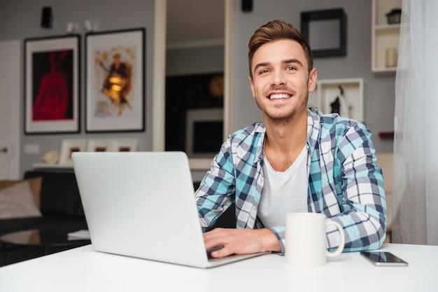 Zdjęcie wesoły młody człowiek ubrany w koszulę w klatce wydruku siedzi w domu i przy użyciu komputera przenośnego.