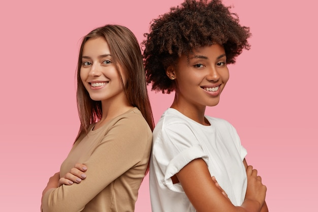 Zdjęcie wesołych, różnorodnych, przyjaznych kobiet stojących plecami do siebie, trzymających ręce skrzyżowane, zadowolonych ze współpracy, ubranych w swobodny strój, odizolowane na różowej ścianie. strzał poziomy