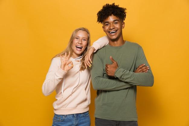 Zdjęcie wesołych studentów mężczyzny i kobiety w wieku 16-18 lat z aparatami ortodontycznymi, śmiejących się i gestykulujących przed kamerą, odizolowane na żółtym tle