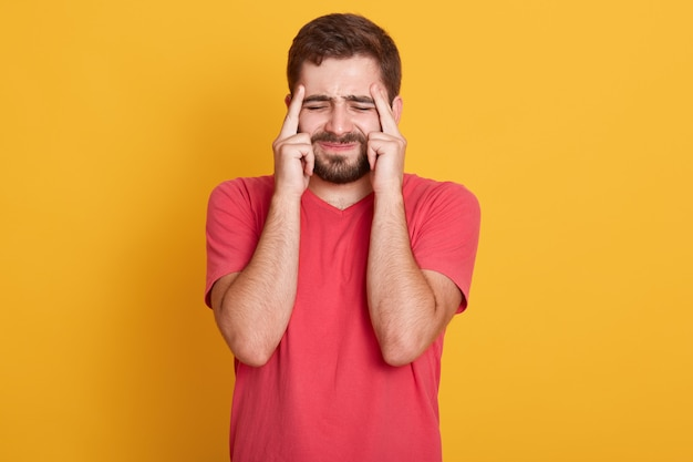 Zdjęcie wewnętrzne niezadowolonego mężczyzny marszczącego brwi, mającego ból głowy, czuje się zmęczony, potrzebuje odpoczynku, zamyka oczy z bólu, trzyma palce na skroniach