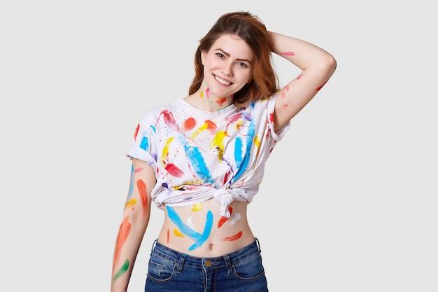 Zdjęcie wewnętrzne szczęśliwej malarzy z europy ma brudne ciało i białą koszulkę z kolorowymi farbami, pokazuje brzuch, trzyma rękę za głową, na białym tle nad białą ścianą tworzy dzieło sztuki lub arcydzieło