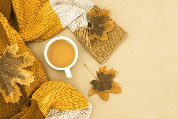 Zdjęcie widoku z góry pomarańczowego swetra z filiżanką herbaty i żółtymi jesiennymi liśćmi i szyszkami sosnowymi na białym tle z pustą przestrzenią