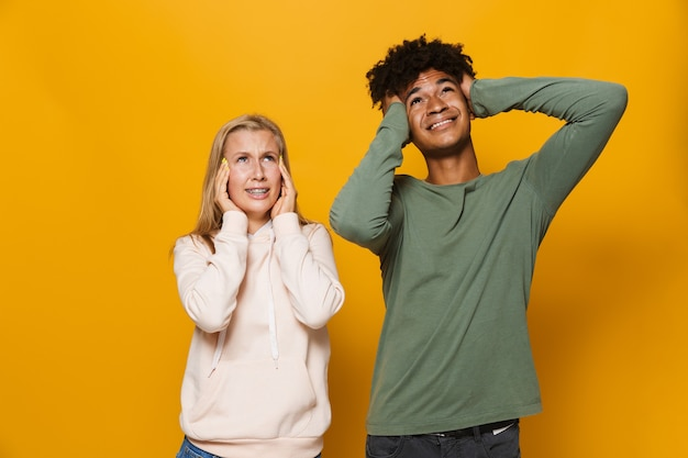 Zdjęcie wieloetnicznej pary mężczyzny i kobiety w wieku 16-18 lat z aparatami ortodontycznymi zakrywającymi uszy w smutku, odizolowane na żółtym tle