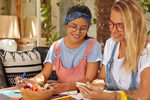 Zdjęcie wieloetnicznych dziewcząt siedzących razem w przytulnym wnętrzu, używających telefonów komórkowych do czytania wiadomości i wiadomości, trzymających długopis, jedzących pyszne egzotyczne danie, zapisujących w organizatorze. różnorodni towarzysze