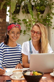 Zdjęcie wieloetnicznych kobiet sprawia, że badania współpracują ze sobą: blondynka w okularach wyszukuje informacje w internecie, podczas gdy jej towarzyszka pisze w zeszycie