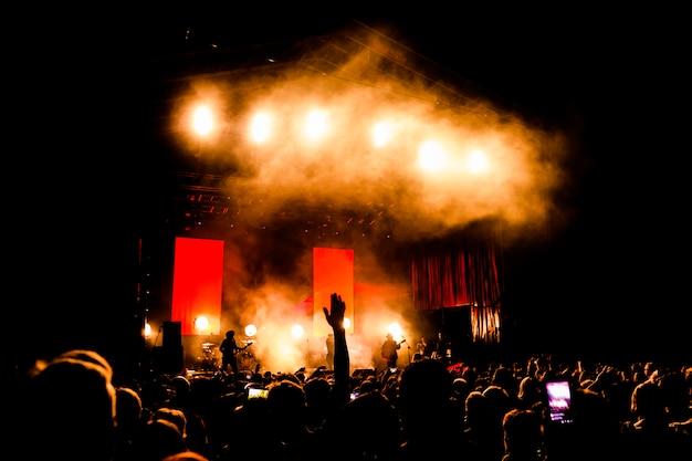 Zdjęcie wielu ludzi cieszących się nocnymi występami, dużego, nierozpoznawalnego tłumu tańczącego z podniesionymi rękami i telefonów komórkowych na koncercie. życie nocne
