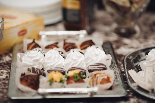 Zdjęcie wielu różnych ciast, babeczek i innych słodyczy na dużym talerzu