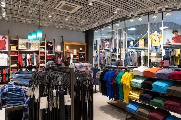 Zdjęcie wnętrza regałów z koszulami, podkoszulkami i dżinsami