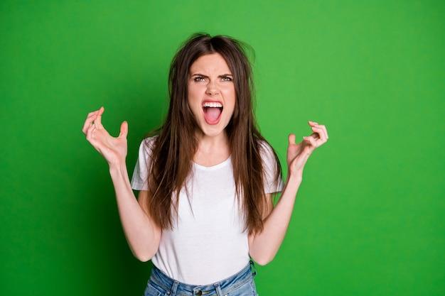 Zdjęcie wściekłej atrakcyjnej dziewczyny nosi białą koszulkę ma problem z włosami, ramionami patrzą w górę na białym tle w kolorze zielonym