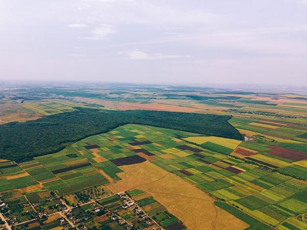 Zdjęcie wykonane dronem nad wioską w pobliżu pól uprawnych w letni dzień.